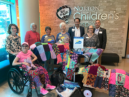 Marlene McComas, Dottie Crouch, and Jenn Williams were joined by Amy Lynn and Michelle Lawson to present the blankets to Norton Children's Hospital Medical Director Mark McDonald MD and Rev. Robin Hogle.
